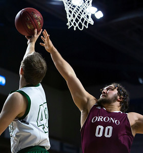 BANGOR, Maine -- 02/25/2017 -- Mount Desert Island's Riley Swanson (left) goes up for two past Orono's Jake Koffman during their Class B boys basketball championship game at the Cross Insurance Center in Bangor Saturday. Ashley L. Conti   BDN