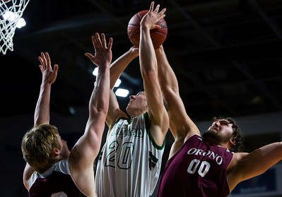 BANGOR, Maine -- 02/25/2017 -- Mount Desert Island's Graham Good (center) tries for two past Orono's Keenan Collett (left) and Orono's Jake Koffman during their Class B boys basketball championship game at the Cross Insurance Center in Bangor Saturday. Ashley L. Conti | BDN