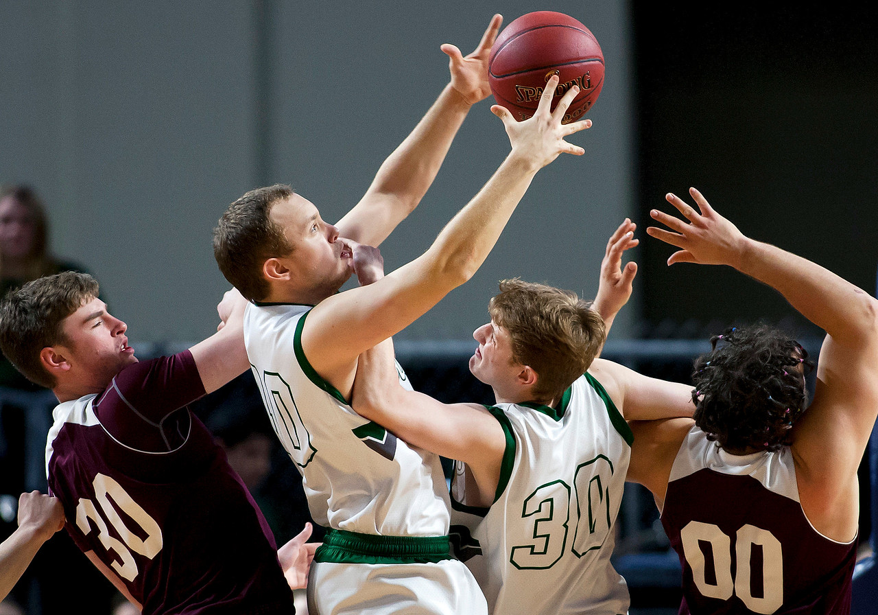 BANGOR, Maine -- 02/25/2017 -- Orono's Connor Robertson (left) and Orono's Jake Koffman (right) battle for a rebound against Mount Desert Island's Riley Swanson (center) and Mount Desert Island's James McConomy during their Class B boys basketball championship game at the Cross Insurance Center in Bangor Saturday. Ashley L. Conti | BDN