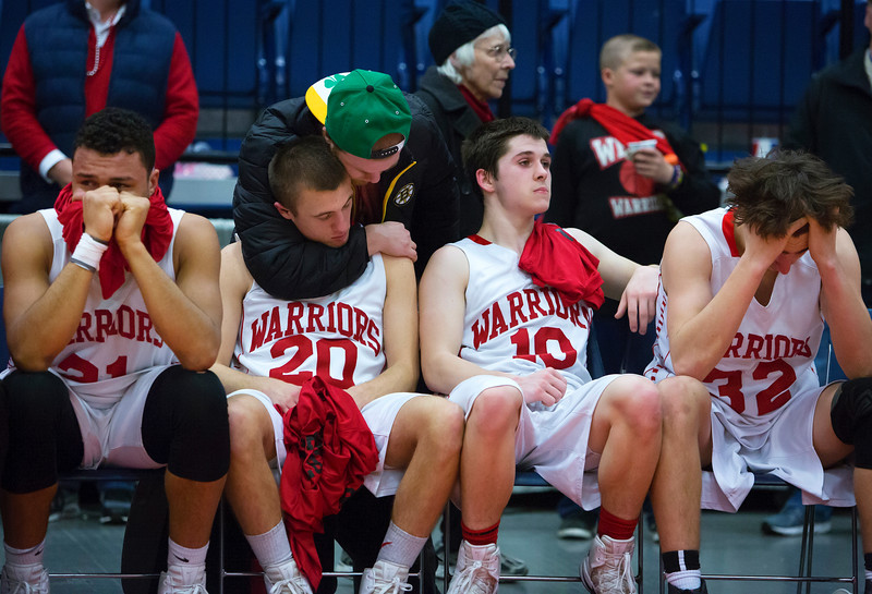 AUGUSTA, Maine -- 03/03/2017 -- Wells' Tyler Dewey (second from left) is confronted after being defeated by Mount Desert Island during their Class B boys basketball state championship at the Augusta Civic Center in Augusta Friday. Ashley L. Conti   BDN
