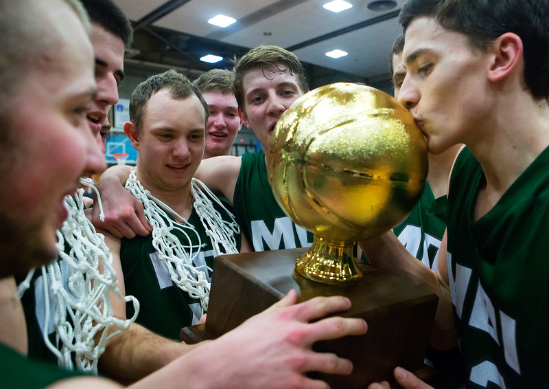 AUGUSTA, Maine -- 03/03/2017 -- Mount Desert Island's Devin M. Parlatore (right) gives the golden ball a kiss after defeating Wells during their Class B boys basketball state championship at the Augusta Civic Center in Augusta Friday. Ashley L. Conti | BDN
