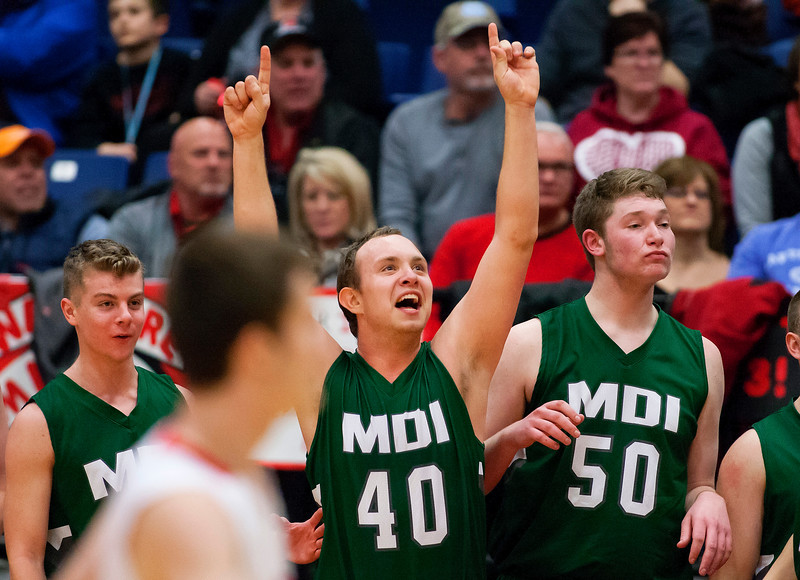 AUGUSTA, Maine -- 03/03/2017 -- Mount Desert Island's Riley Swanson (center) holds his hands in the air as time runs out to give his team the win against Wells during their Class B boys basketball state championship at the Augusta Civic Center in Augusta Friday. Ashley L. Conti | BDN