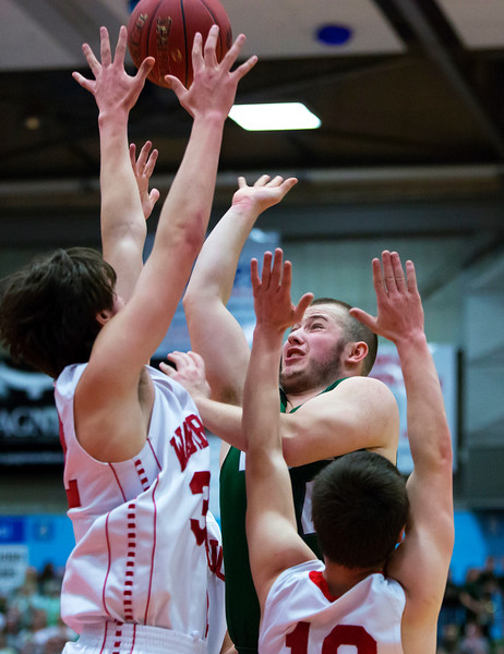 AUGUSTA, Maine -- 03/03/2017 -- Mount Desert Island's Aaron Snurkowski (center) goes up for two past Wells' Cameren Cousins (left) and Wells' Riley Dempsey during their Class B boys basketball state championship at the Augusta Civic Center in Augusta Friday. Ashley L. Conti | BDN