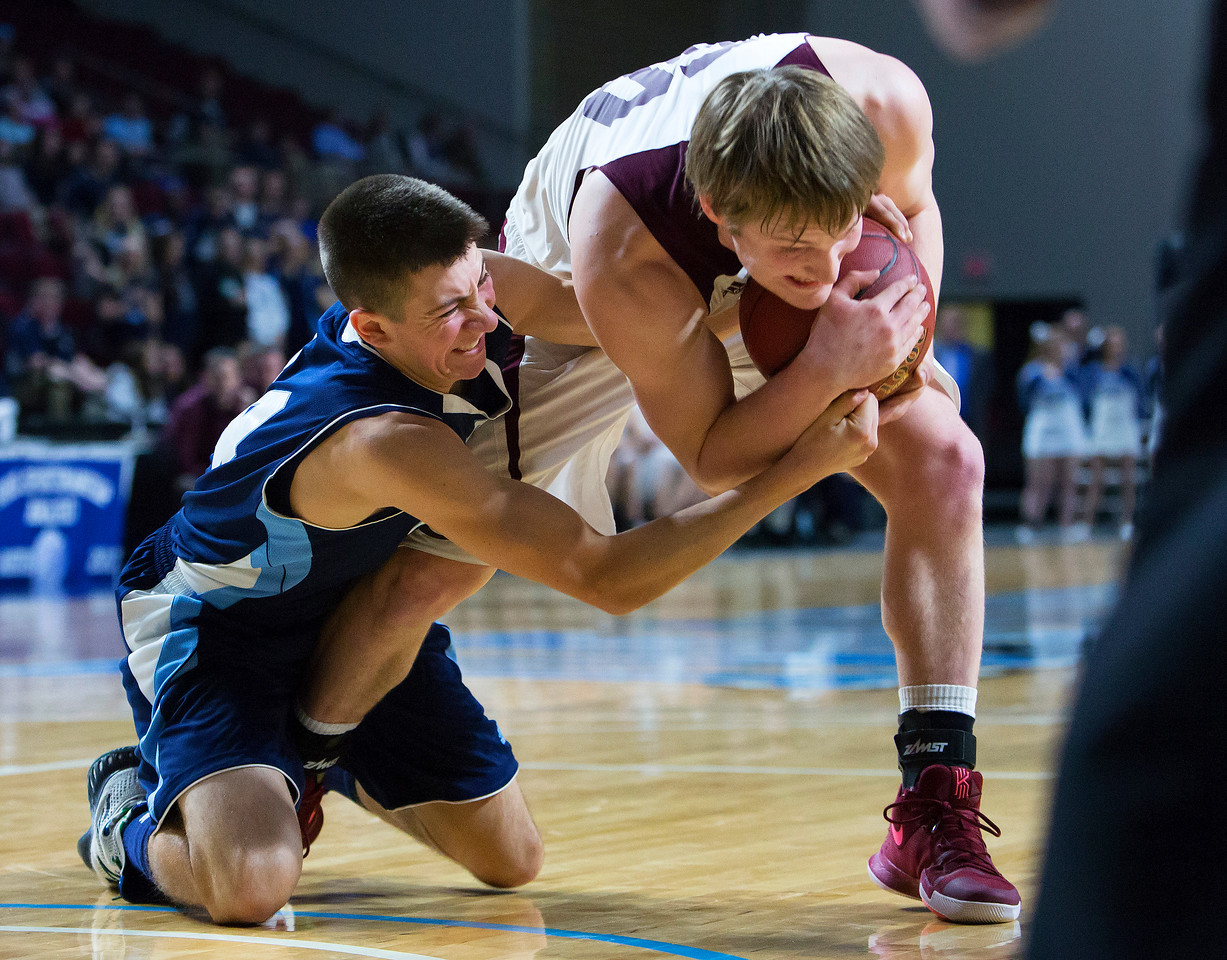 BANGOR, Maine -- 02/18/2017 -- Presque Isle's Jonah G. Hudson (left) battles for a loose ball against Orono's Keenan Collett during their Class B boys basketball quarterfinal game at the Cross Insurance Center in Bangor Saturday. Ashley L. Conti | BDN