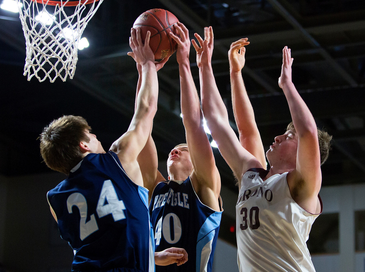 BANGOR, Maine -- 02/18/2017 -- Presque Isle's Jacob J. Kinney (left) and teammate Presque Isle's Bradley R. Kinney (center) battle for a rebound against Orono's Connor Robertson during their Class B boys basketball quarterfinal game at the Cross Insurance Center in Bangor Saturday. Ashley L. Conti | BDN