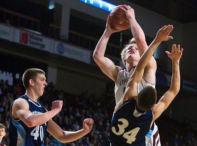 BANGOR, Maine -- 02/18/2017 -- Orono's Keenan Collett (center) fouls Presque Isle's Jonah G. Hudson while trying for two during their Class B boys basketball quarterfinal game at the Cross Insurance Center in Bangor Saturday. Ashley L. Conti | BDN