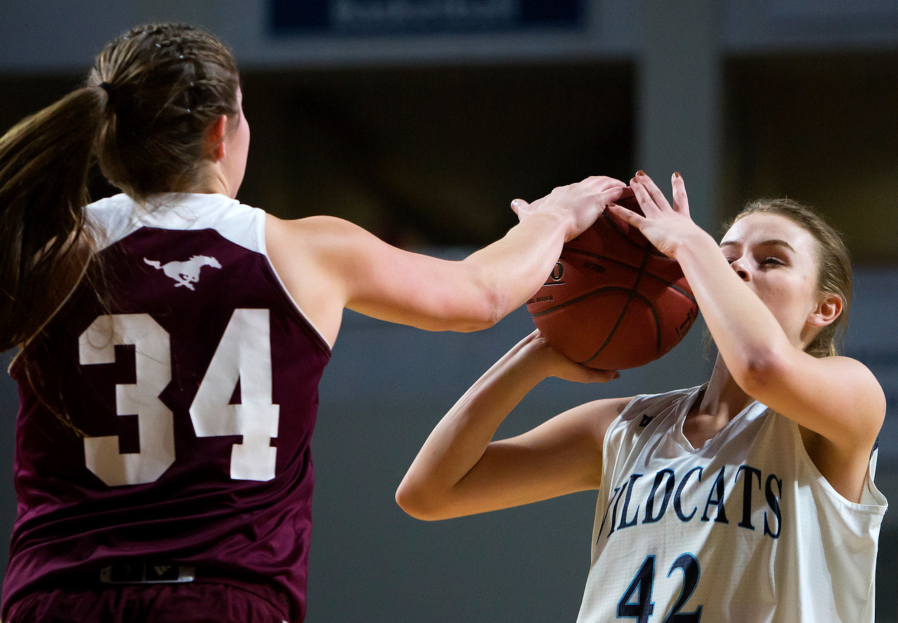 BANGOR, Maine -- 02/22/2017 -- Foxcroft Academy's Mackenzie Beaudry (left) blocks a shot attempt from Presque Isle's Molly A. Kingsbury during their Class B girls basketball semifinal game at the Cross Insurance Center in Bangor Wednesday. Ashley L. Conti | BDN