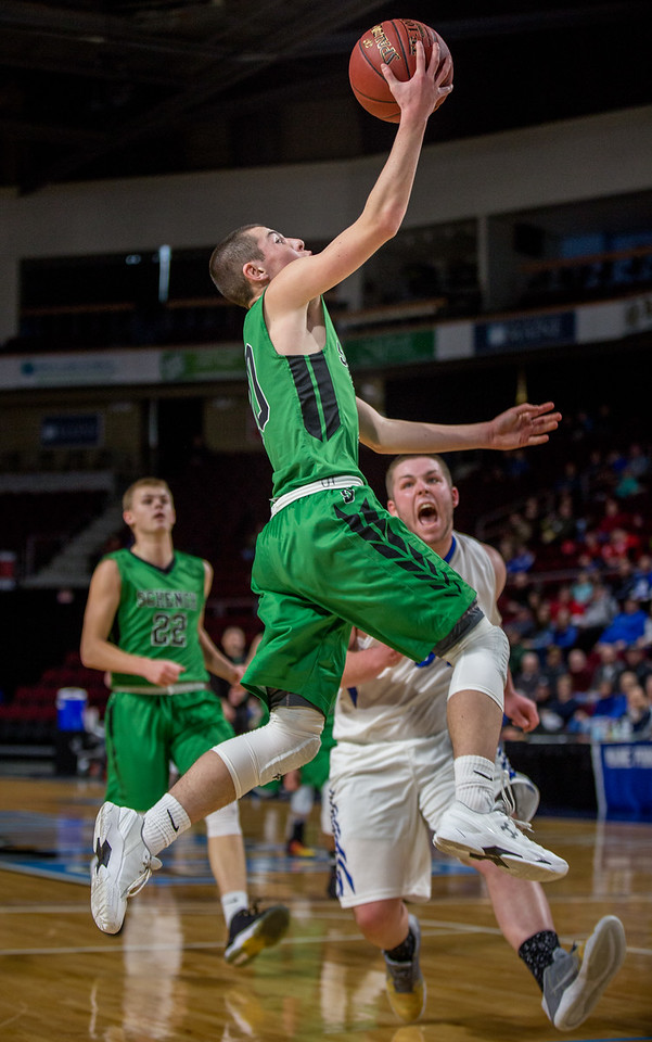 BANGOR, MAINE -- 02/21/2017 -- Schenck's Riley Dionne (front) jumps for the basket as Hodgdon's Dillon Buzzell screams out during their Class C North Quarterfinal game at the Cross Insurance Center in Bangor on Tuesday morning. Micky Bedell   BDN