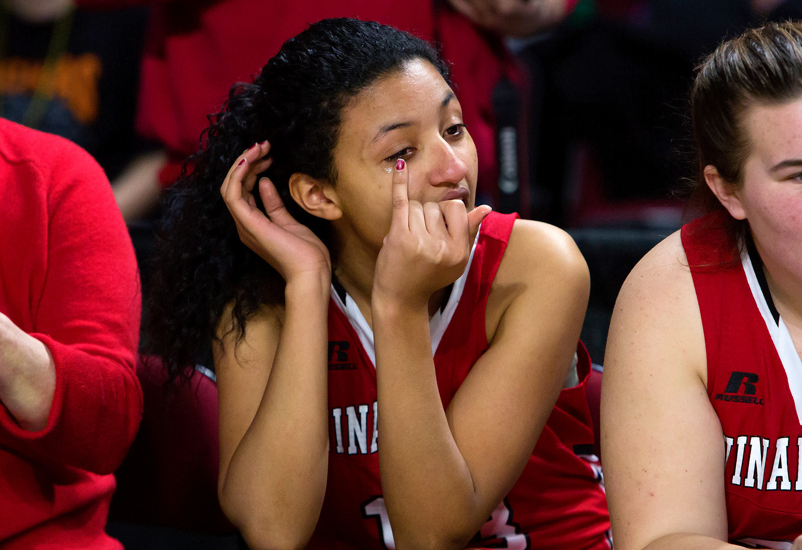 BANGOR, Maine -- 03/04/2017 -- Vinalhaven's Rosanna Morel (center) wipes a tear from her eye after defeating Shead during their Class D girls basketball state championship at the Cross Insurance Center in Bangor Saturday. Ashley L. Conti | BDN