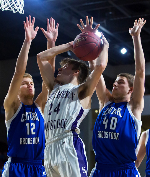 BANGOR, Maine -- 02/23/2017 -- Southern Arroostook's Robert J. Lillis (center) tries for two past Central Aroostook's Zach Crouch (left) and Central Aroostook's Clark Bradbury during their Class D boys basketball semifinal game at the Cross Insurance Center in Bangor Thursday. Ashley L. Conti | BDN