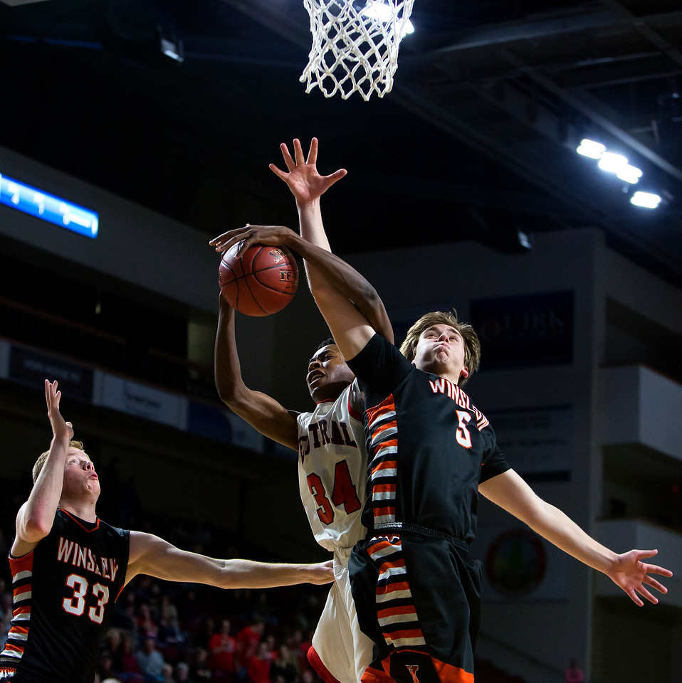 BANGOR, Maine -- 02/17/2017 -- Central's Dylan B. Gray (center) gets tangled in Winslow's Hunter Campbell while going for a rebound during their Class B boys basketball quarterfinal game at the Cross Insurance Center in Bangor Friday. Ashley L. Conti | BDN