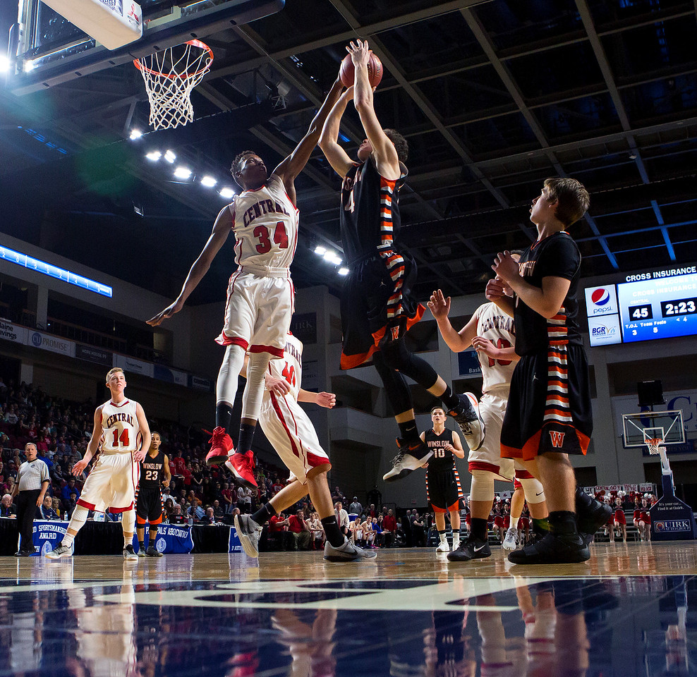 BANGOR, Maine -- 02/17/2017 -- Central's Dylan B. Gray (left) blocks a shot from Winslow's Dylan Hutchinson during their Class B boys basketball quarterfinal game at the Cross Insurance Center in Bangor Friday. Ashley L. Conti | BDN