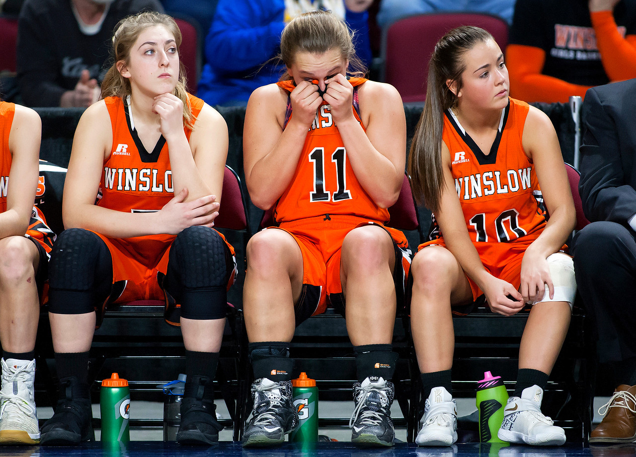 BANGOR, Maine -- 02/18/2017 -- Winslow's Heather Kervin (center) wipes tears from her eyes as time expires during their Class B girls basketball quarterfinal game against Hermon at the Cross Insurance Center in Bangor Saturday. Hermon won. Ashley L. Conti | BDN