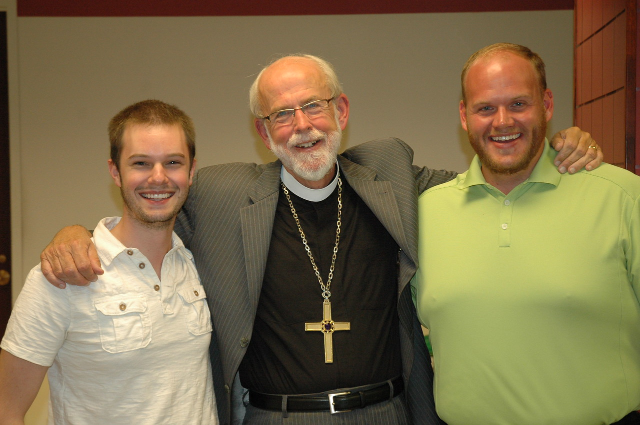 Presiding Bishop Mark S. Hanson surrounded by the Rev. Alex Raabe and Eric Peterson