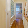 Hallway with cherry flooring, display cabinet and recycled glass block bringing light to stairway.
