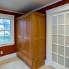 Mudroom with custom armoire. Door to full bathroom.