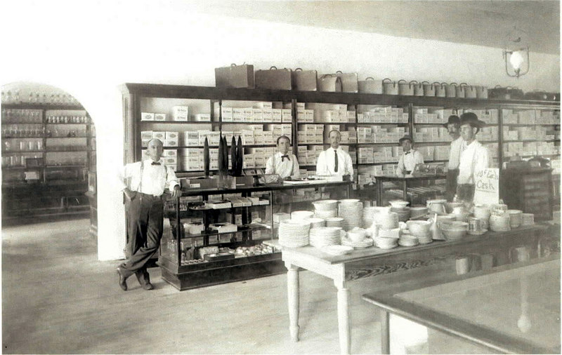 R. L. Patten & Company general merchandise store. Bob Patten leaning on a counter in his store. W. M. Pafford and W. P. Dorsey are standing behind the countere. Photo circa 1910 in Milltown, Georgia