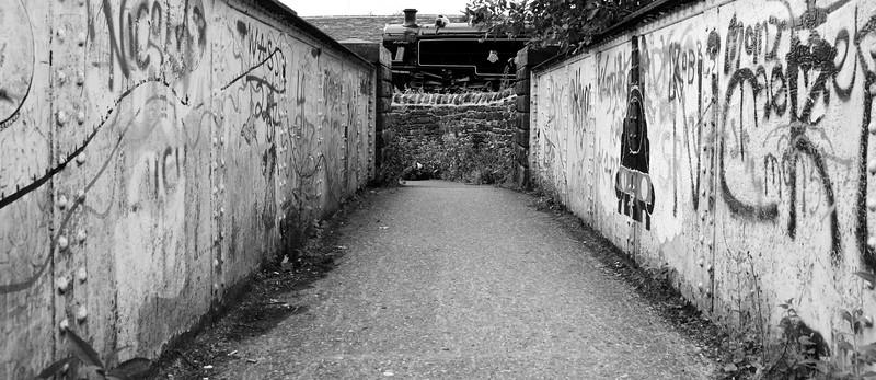 Keighley and Worth Valley Railway train passing graffiti bridge near Ingrow