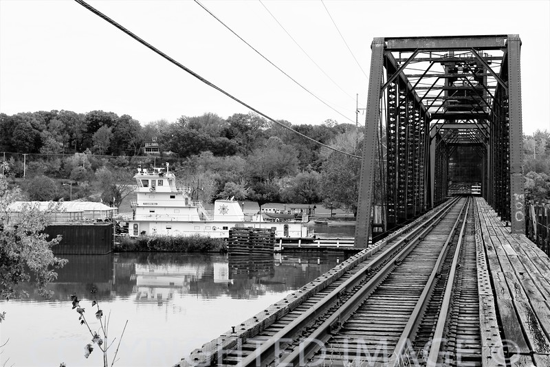 "Tow boat & barges move upstream on the Illinois River at Ottawa, IL. The ""lift"" railroad bridge at right dates to the late 1890s & a middle section lifts to accommodate the barge traffic."