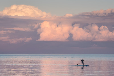 "GRAND MARAIS 8601  ""Grand Marais SUP'er""  A stand-up paddleboarder paddles across the Grand Marais, Minnesota harbor entrance in front of some beautiful summer sunset clouds.  I noticed he was not wearing a life jacket or any kind of wet or dry suit... definitely NOT recommended on Lake Superior!  The water is very cold; I guess he figured he wasn't very far from shore so he could have made it back to shore rather easily before hypothermia set in if he had fallen off.  Perhaps the little bundle on the front of the board is a life jacket?  That's better than nothing, I guess, but the life jacket isn't much good if you're not wearing it."