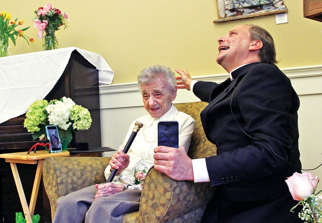 ". Here Father Jeremy St. Martin from St. John\'s Catholic Church, gives Dorothy ""Dot\"" Manceau a blessing during his closing prayer after she received the Boston Post Cane. Nashoba Valley Voice Photo by David H. Brow"