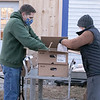 Volunteers Rick Bailey and Laura Noble stock the tables outside on Friday, November 20, 2020 at the Townsend Ecumenical Outreach center's food distribution. SENTINEL & ENTERPRISE/JOHN LOVE