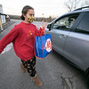 Volunteer Elizabeth Kelly, 13, carries a bag of groceries out to a waiting car on Friday, November 20, 2020 at the Townsend Ecumenical Outreach center. SENTINEL & ENTERPRISE/JOHN LOVE