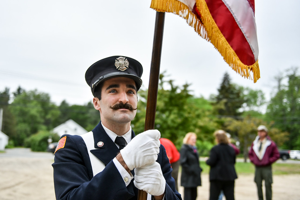 . Townsend firefighter Andrew Shepherd poses stands with an American flag during Sunday\'s Memorial Day parade in Townsend.  SENTINEL & ENTERPRISE JEFF PORTER