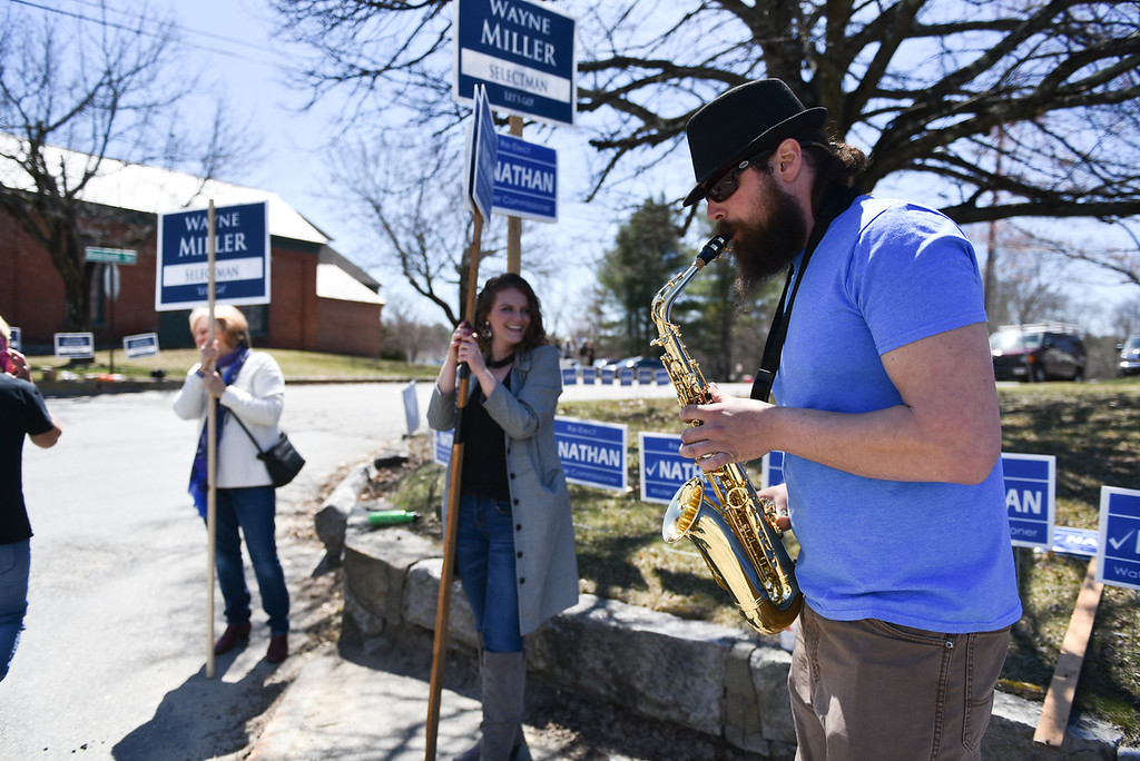 . Nathan Mattel, who is up for re-election for water commissioner in Townsend, plays the saxophone alongside girlfriend Vanessa Howard during the town elections on Monday.  SENTINEL & ENTERPRISE JEFF PORTER