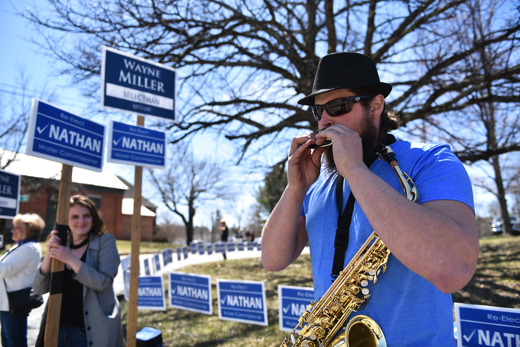 . Nathan Mattel, who is up for re-election for water commissioner in Townsend, plays the harmonica alongside girlfriend Vanessa Howard during the town elections on Monday.  SENTINEL & ENTERPRISE JEFF PORTER