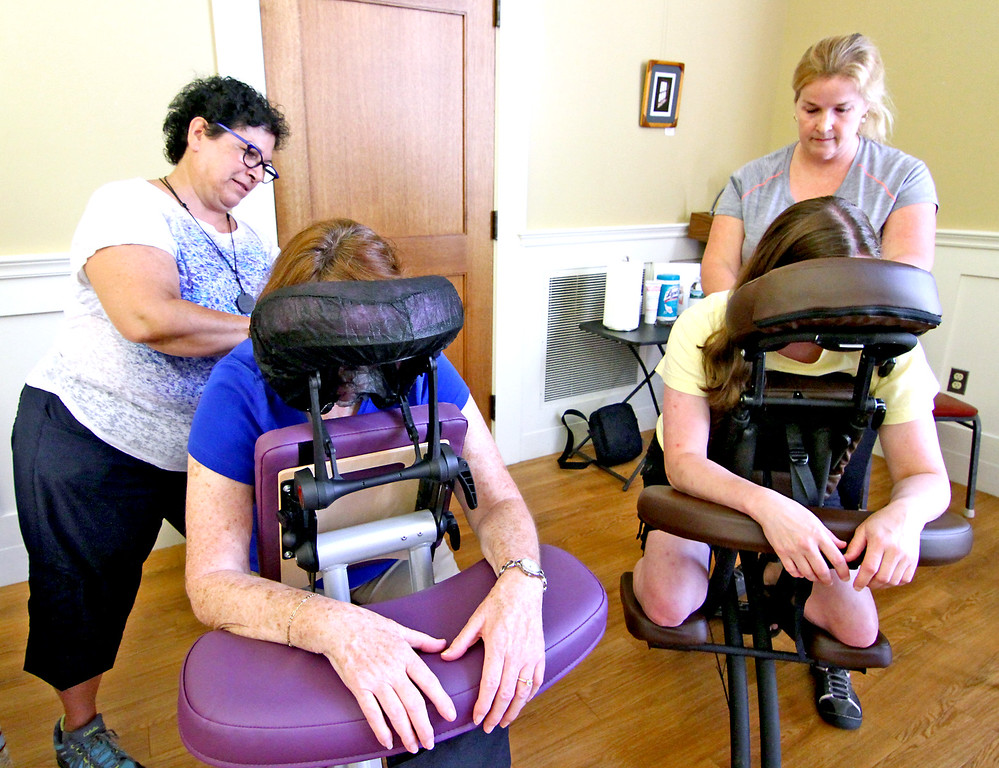 . Giving a massage to locals is L-R, Therese Palazzo, (working on Cheryl Simoneau of Townsend) and Kathleen Avison, (owner of Kathleen Avison Massage Therapy of Townsend) to Andrea Pierce of Ashby, they are at the National Night Out in Townsend. Nashoba Valley Voice Photo by David H. Brow