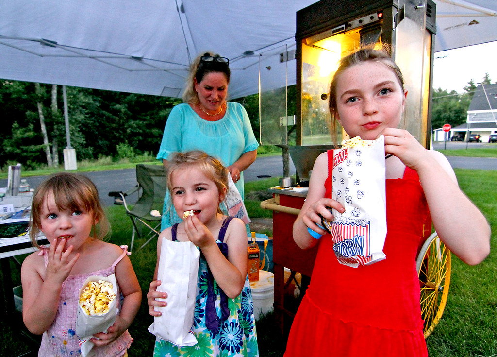 . Enjoying some fresh popped Pop Corn made by Cynthia Donovan in back, are kids L-R, Sadie Schuster,4, Gabrille Maney,5, and Naomi Maney, 9. Nashoba Valley Voice Photo by David H. Brow