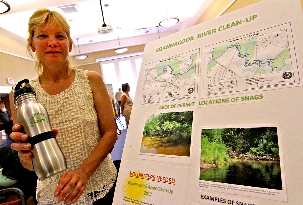. Karen Hill, with Conservation and Squannacook River Clean Up, shows a poster of some of the work volunteers have done as she holds one of the water bottles the group are selling to raise funds to help clean up the river. Nashoba Valley Voice Photo by David H. Brow