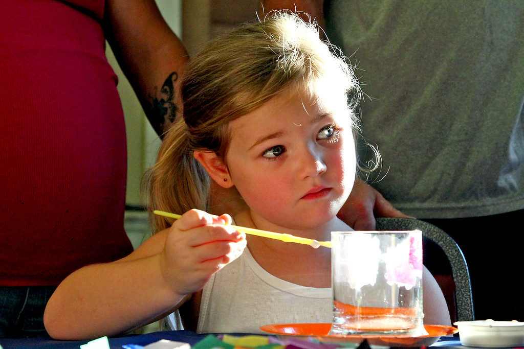 . Young Savannah Hills, 5, looks over to a Townsend Recreation workers doing arts & crafts, as she paints a jar for an electric candle holder. Nashoba Valley Voice Photo by David H. Brow
