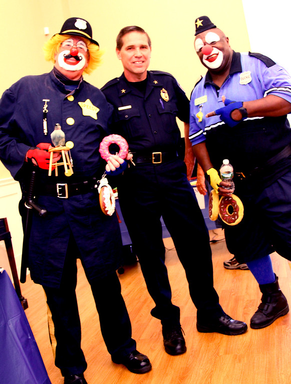 ". Townsend Police Chief Rick Bailey (middle) hams it up with clowns L-R, Jim ""Speedy\"" Reedy, and Shelton \""Duckie\"" Dobson from Aleppo Shriners Clown Unit at National Night Out in Townsend. Nashoba Valley Voice Photo by David H. Brow"