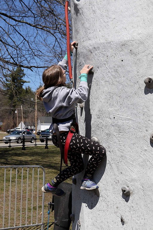 . Madison Pitre, 11, from Gardner makes her way up the rockwall they had on the Townsend common Saturday during Townsend\'s Earth Day event. SENTINEL & ENTERPRISE/JOHN LOVE