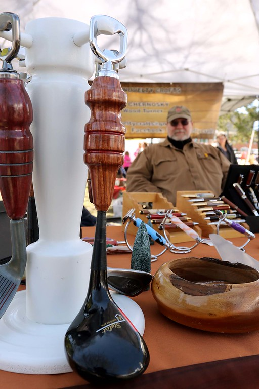 . Tim Chernosky from Townsend sits behind his wood and acrylic crafts he makes at his booth on the Townsend common Saturday during Townsend\'s Earth Day event. This item he made from a golf driver is a can opener. He calls his business Tim\'s Novelty Crafts. SENTINEL & ENTERPRISE/JOHN LOVE