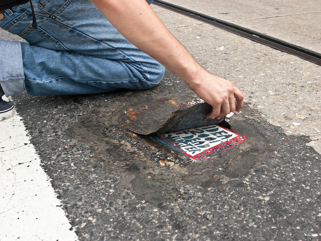 Colin Smith uncovering a tile at 12th and Market Streets Philadelphia.