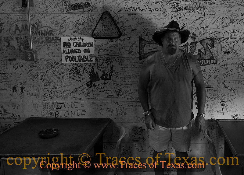 Title:Home Away From Home <br /> <br /> Comments: One of the friendly owners of Mynar's Bar in West, wearing the hat with beer bottle cap brim that they normally only take down for special occasions. <br /> <br /> Location: West, Texas