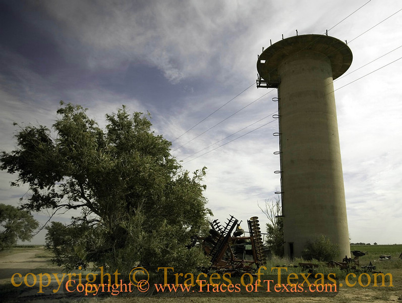 Title:   Juxtaposition<br /> <br /> Comments: This water tower and a small chapel are all that remains of a World War II prisoner of war camp near Hereford that housed nearly 4,000 Italian prisoners of war. I liked the way farm implements now surround it.  Way to turn those swords into plowshares, Texas!<br /> <br /> Location: near Hereford, Texas