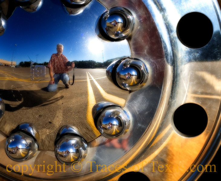 Title: Self-Portrait in Bus Wheel<br /> <br /> Comments: It isn't easy being pretty. <br /> <br /> Location:  Waco