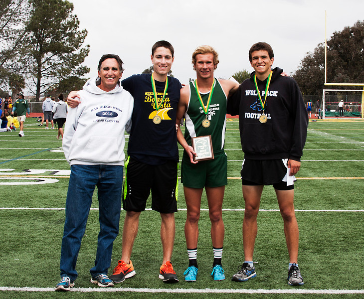 The top three boy finishers in the Thom Hunt mile at the Elmer Runge classic were Erik Armes (holding plaque), who finished first. The second place finisher was Nick Famolaro from West Hills (Wolf Pack top). Third was Austin Johnson from Bonita Vista. Thom Hunt himself is in the white Mesa hoodie. He is the head Cross Country and distance coach at Mesa College in San Diego.