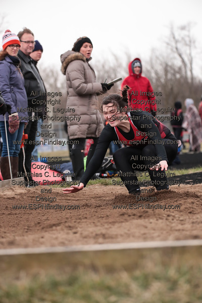 Arlington's Alyssa Jordan leans forward as she lands in the long jump pit.