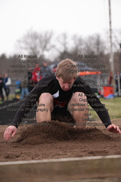 McComb's Tanner Schroeder lands in the long jump pit.