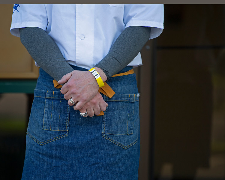 Caption: Chef Marc Therrien closeup with Keeneland log, bluejean apron and yellow wrist band received upon clearance at the security screening locations upon entering.<br /> Behind the Scenes at Keeneland during Covid19 virus and the people, horses, and essentials needed to take care of race horses on April 2, 2020 Keeneland in Lexington, KY.