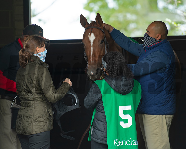 (L-R): The training team with Katey Caddel holding blinkers and Robbie Medina calming horse. .Robbie Medina saddles and watches #5 Bakers Bay with Tyler Gaffalione in allowance Race 5  at Keeneland on October 18, 2020.