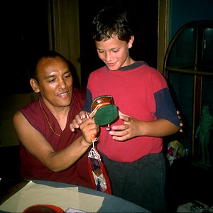 Tibetan Monk Showing a Boy Tools Used to Create a Mandala (San Antonio, TX)
