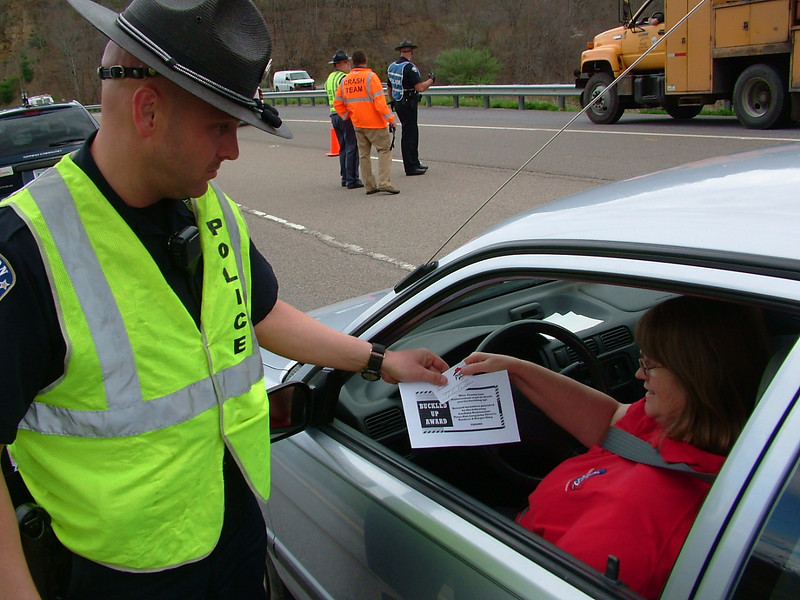 """A Coeburn Police Officer hands out a """"Buckle Up Award"""" to a motorist, coupons for a pizza and drinks for obeying the law and buckling up during Operation 58 near Coeburn April 21, 2008."""