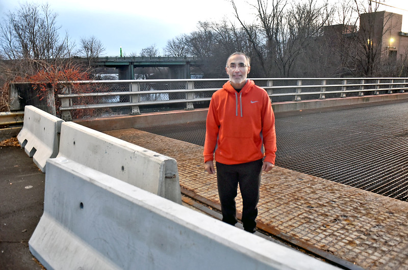 Dracut resdent Tom Salem, stands on the now closed Beaver SAtreet Bridge in Lowell, in background is a view of the VFW Highway with bridge under construction. SUN/ David H. Brow