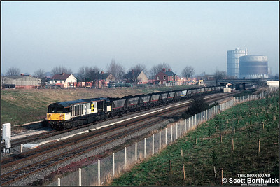 58001 departs from Three Spires Jnct, Coventry with 7V44 0925 Three Spires Jnct-Didcot Power Station on 25/02/1992. Note the bodyside door from a Red Stripe Railfreight liveried locomotive.